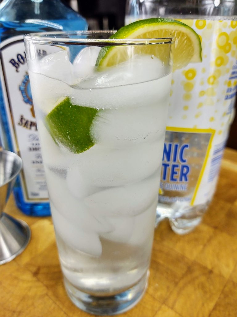 gin and tonic in highball with lime wedges